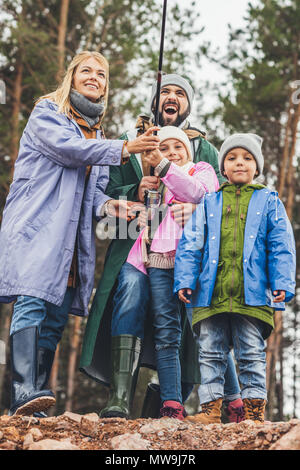 happy young family in raincoats fishing together - Stock Photo