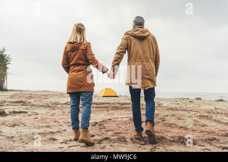 couple holding hands and looking at camping tent on sandy beach - Stock Photo