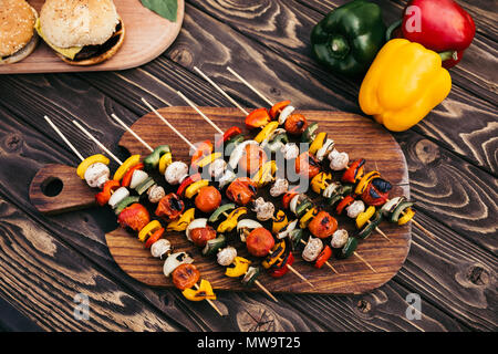 Cut vegetables on skewers cooked outdoors on grill - Stock Photo