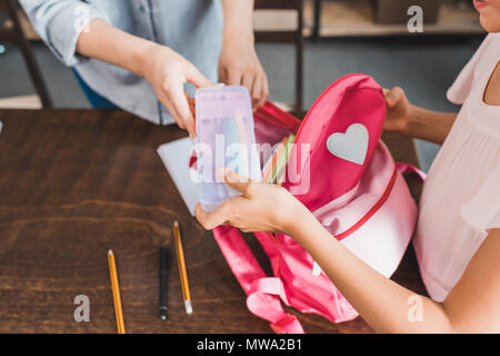 cropped shot of mother and daughter packing stuff in backpack for school - Stock Photo