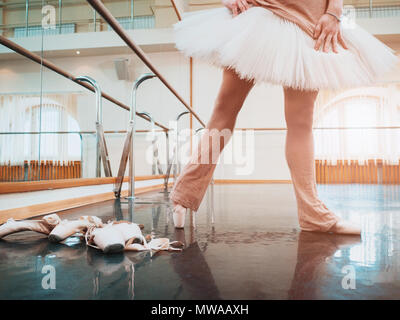 Ballerina in ballet pointe and white tutu stretches on barre in gym. Woman practicing in dance studio. Work out of young girl. - Stock Photo