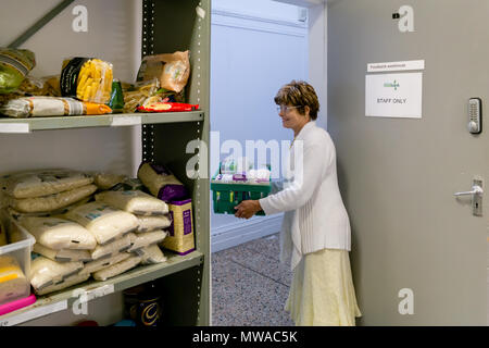 A local church food bank (part of Trussell Trust) dealing with period poverty - a female volunteer offers clients a selection of sanitary products - Stock Photo