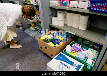A local church food bank (part of Trussell Trust) dealing with period poverty: a female volunteer sorts stock besides a selection of sanitary products - Stock Photo
