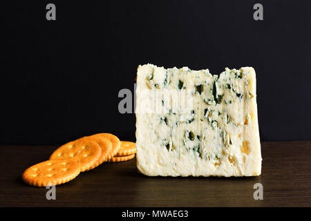 Slices of Danish Blue cheese and cookies on an old wooden table. - Stock Photo