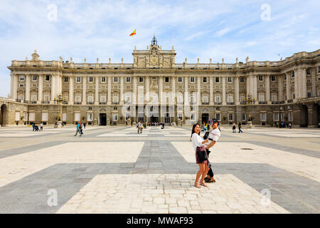 Young Chinese tourist couple posing for selfie at The Royal Palace Palacio Real de Madrid. official residence of the Spanish Royal Family. Calle de Ba - Stock Photo