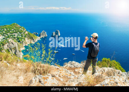 young caucasian tourist taking picture of famous faraglioni rocks in sea with his smartphone on top of Mount Solaro after hiking up the trail on Capri - Stock Photo