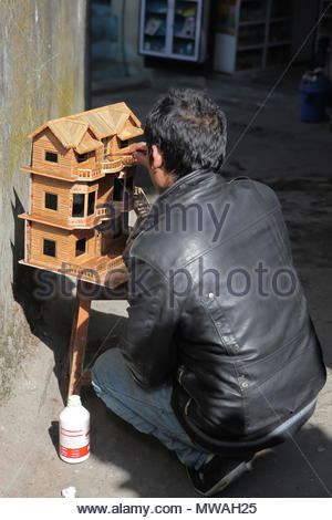 Man paints a final coat of vanish on a small decorative wooden house he has just constructed in the city of Gangtok, Sikkim, India. - Stock Photo