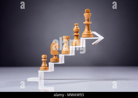 Wooden Chess Piece On Increasing Zigzag Arrow Against Grey Backdrop - Stock Photo