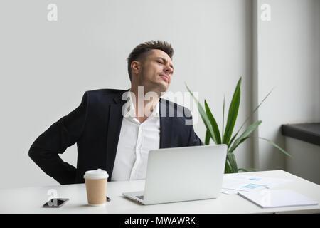 Businessman touching aching back feeling backache after sedentar - Stock Photo
