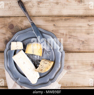 On the plate are different cheese for the party. Vintage photo. Wooden background. Copy space - Stock Photo