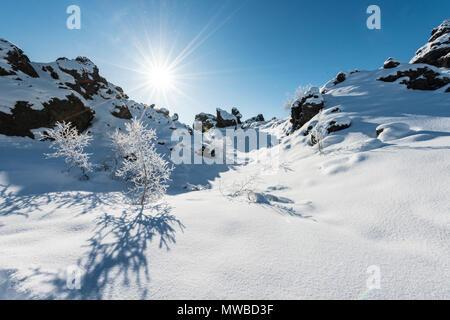 Sun shines on snow-covered lava field, snowy landscape, volcanic landscape Krafla, Dimmuborgir National Park, Mývatn, Iceland - Stock Photo