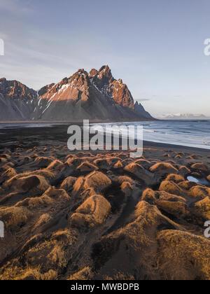 Black sandy beach, overgrown stones, mountains Klifatindur, Eystrahorn and Kambhorn, headland Stokksnes, massif Klifatindur - Stock Photo