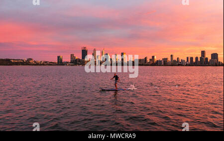 A man stand up paddleoarding on the Swan River with Perth city in the distance. Western Australia - Stock Photo