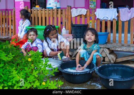 Kanchanaburi, Thailand - September 8, 2016: Kindergarten kids in rural nursery school washing dishes, bowls and table ware in black basin after lunch