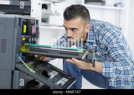 repairman fixing cartridge in photocopy machine at office - Stock Photo