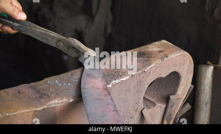 Blacksmith working metal with hammer on the anvil in the forge. hammer forging hot iron at anvil. Blacksmiths make machete. Hands of the smith by the work. Philippines. - Stock Photo