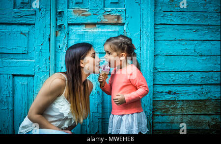little girl with mother eating ice cream on a beautiful turquoise background of wood - Stock Photo
