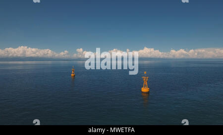 Orange buoy in the blue sea on a background of blue sky, clouds, island. Aerial view:navigational buoy in the ocean.Philippines, Cebu. Travel concept. - Stock Photo