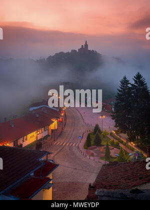 Amazing beautiful view over Tsarevets Fortress in Veliko Tarnovo, Bulgaria on a foggy sunrise in summer. Stock Photo