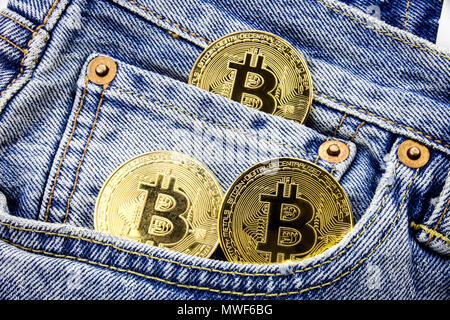 Three golden bitcoin coins on the pockets of the jeans. Concept of making money with online business. Making money motivational message. Online making money with bitcoins. - Stock Photo