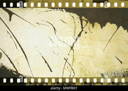 Grunge dripping cracked film strip frame in sepia tones. Damaged wall surface. - Stock Photo
