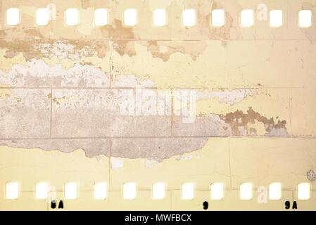 Grunge dripping cracked film strip frame in sepia tones. Damaged brick wall surface. - Stock Photo