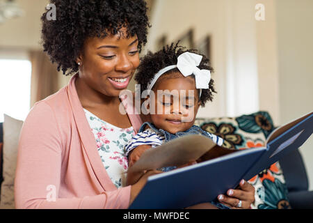 Mother reading a book to her little girl. - Stock Photo