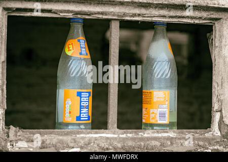 Irn Bru bottles on a broken window frame - Stock Photo