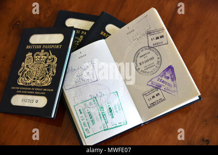 antique timber desk with blue british passports, one open to show stamps, names blanked out - Stock Photo