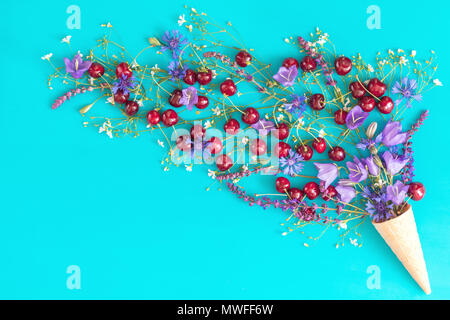 Waffle cone with red cherries, cornflower, blue bells and white flowers blossom bouquets on blue surface. Flat lay, top view sweet food floral backgro