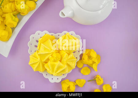 Yellow meringue on a lilac background in a tea serving with a white kettle. Copy spase - Stock Photo