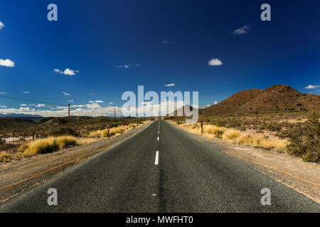 Receding road lane markings in the landscape, garden route, south africa - Stock Photo