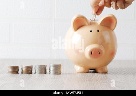 Hand insert coin in a pig. Piggy bank on the wooden table and coins stacks. Saving concept and select focus shallow depth of field with blurred backgr - Stock Photo