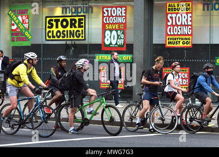Cyclists wait at a road junction by a Maplin store on the north side of Waterloo Bridge on The Strand in London with closing down signs. The electroni - Stock Photo