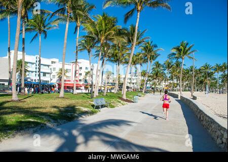 MIAMI - DECEMBER 27, 2017: Morning joggers on the beachfront boardwalk promenade at Lummus Park in South Beach. - Stock Photo