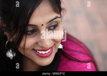 Beautiful Indian woman in traditional clothing, smiling at camera. - Stock Photo
