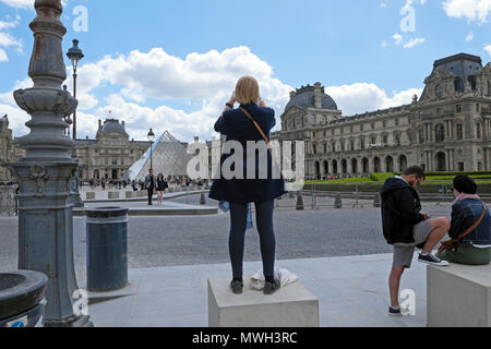 Paris, France - Rear view of female tourist photographing the pyramid building at the Louvre in Europe EU   KATHY DEWITT - Stock Photo