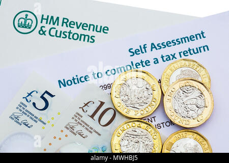 HM Revenue & Customs HMRC Self Assessment Notice to complete a UK tax return with new pound coins and notes money to pay taxes. England UK Britain - Stock Photo