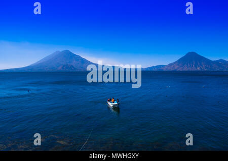 Beautiful outdoor view of small boats in Atitlan Lake is the deepest lake in all of Central America with a maximum depth of about 340 meters, with volcano in Background in Guatemala - Stock Photo
