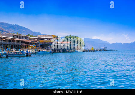 Panajachel, Guatemala -April, 25, 2018: Outdoor view of boats on the shore, small village in the background on the shore, Atitlan lake - Stock Photo