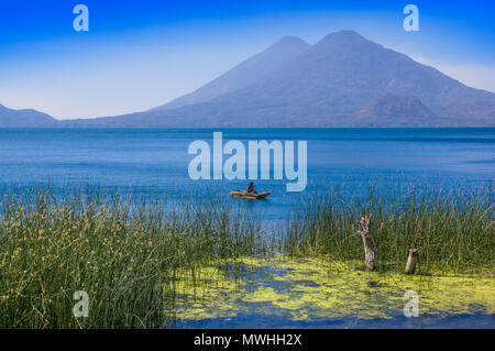 Outdoor view of totora acuatic plants in the border of the lake, with unidentified fisherman in a small boats in Atitlan Lake, with San Pedro volcano in Background - Stock Photo