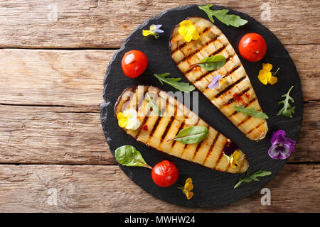 Portion of grilled eggplant and tomato with herbs and edible flowers close-up on the table. horizontal top view from above - Stock Photo