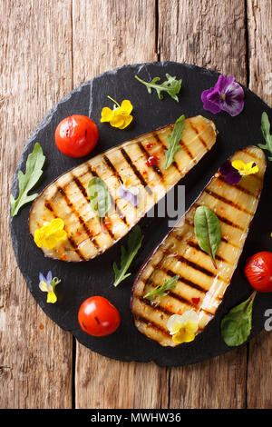 Organic food: grilled eggplant and tomatoes with herbs and edible flowers close-up on the table. Vertical top view from above - Stock Photo