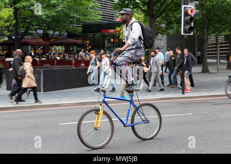 LONDON, UK - MAY 24, 2018 : A man riding a 'double-decker' custom made bicycle in the London Bridge area. - Stock Photo