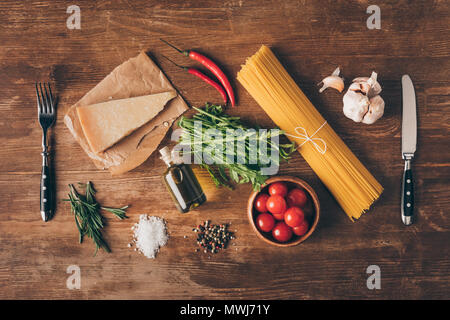 top view of row pasta, fresh ingredients, Parmesan, fork and knife on wooden table - Stock Photo