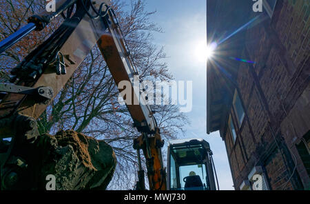 large excavator shovel in the backlight filled with a mighty load of loose brown sand at the construction site, germany - Stock Photo