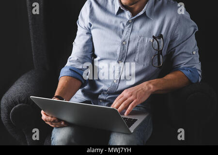 cropped view of man using laptop while sitting in armchair - Stock Photo