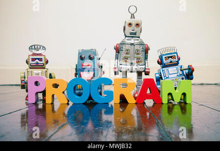 the word PROGRAM with wooden letters and retro toy robots  on an old wooden floor with reflection - Stock Photo