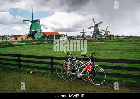 Zaanse Schans, Netherlands - 26 April, 2017: Bicycles parked close to fence against authentic Zaandam mills in Zaanstad village on the river Zaan Land - Stock Photo