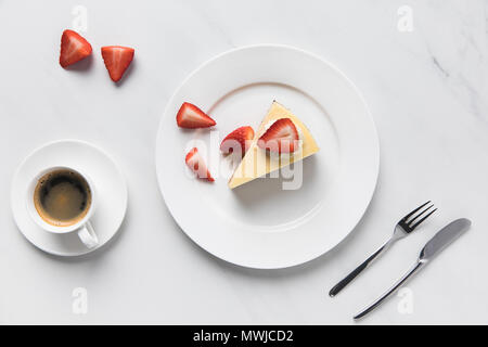 Top view of coffee cup with strawberry cheesecake on plate - Stock Photo